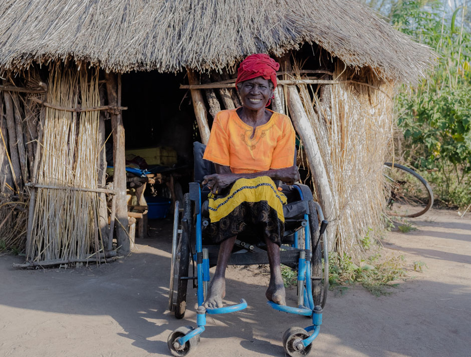 A woman in a wheelchair outside a shack made out of straw.