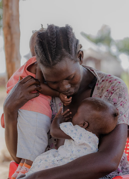 A South Sudanese mother hugs her twins in Uganda