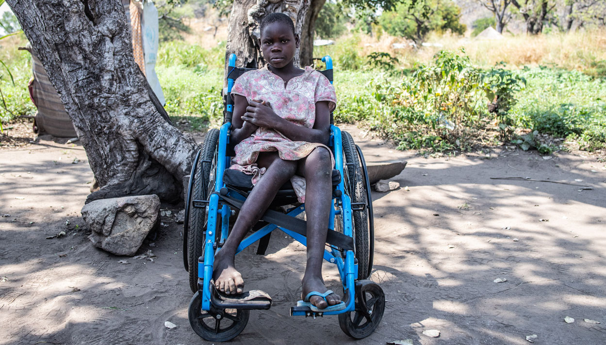 A South Sudanese girl in a blue wheel chair in front of a tree in Uganda.
