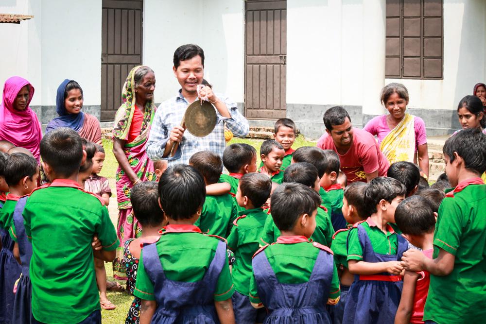 A Bangladeshi teacher stands in front of children wearing green school uniform.