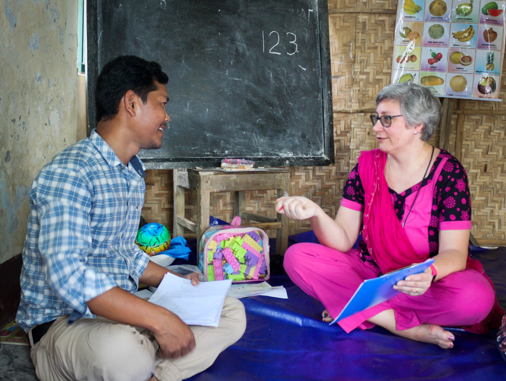 A man in a blue shirt and a woman in a pink top sit together and talk about education.