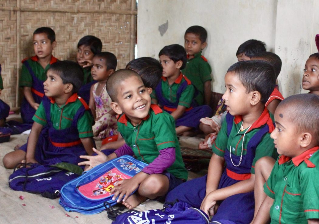 A child in green uniform smiles and looks at his friend in a preschool in Dhaka, Bangladesh.