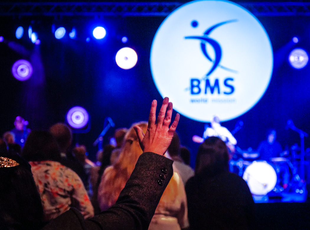 Hand raised with BMS Logo in background