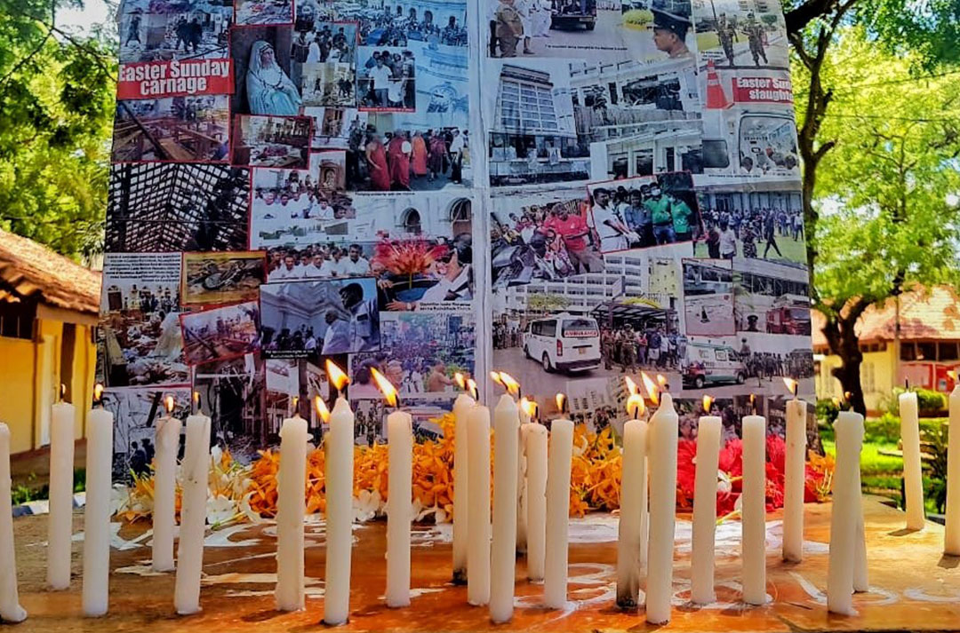 candles in front of photos of Sri Lanka Easter Sunday bombing victims