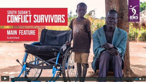 South Sudan's Conflict Survivors main feature with subtitles stil image showing a wheelchair, a boy, and a man under a tree