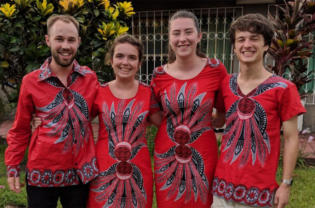 Four young people wearing bright red prints from Mozambique