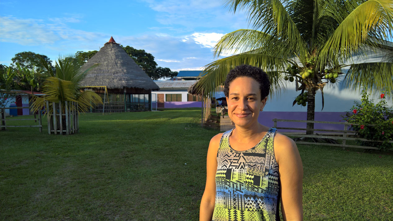 A woman standing in front of a hut