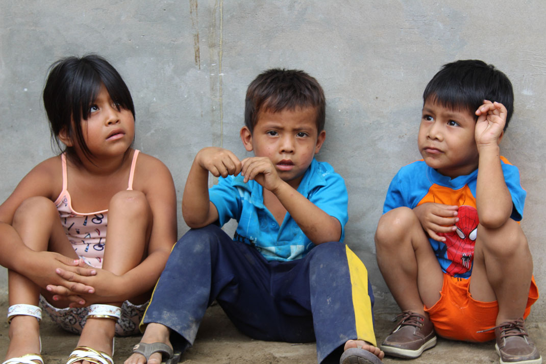 Three children with different expressions sitting down in front of a grey wall