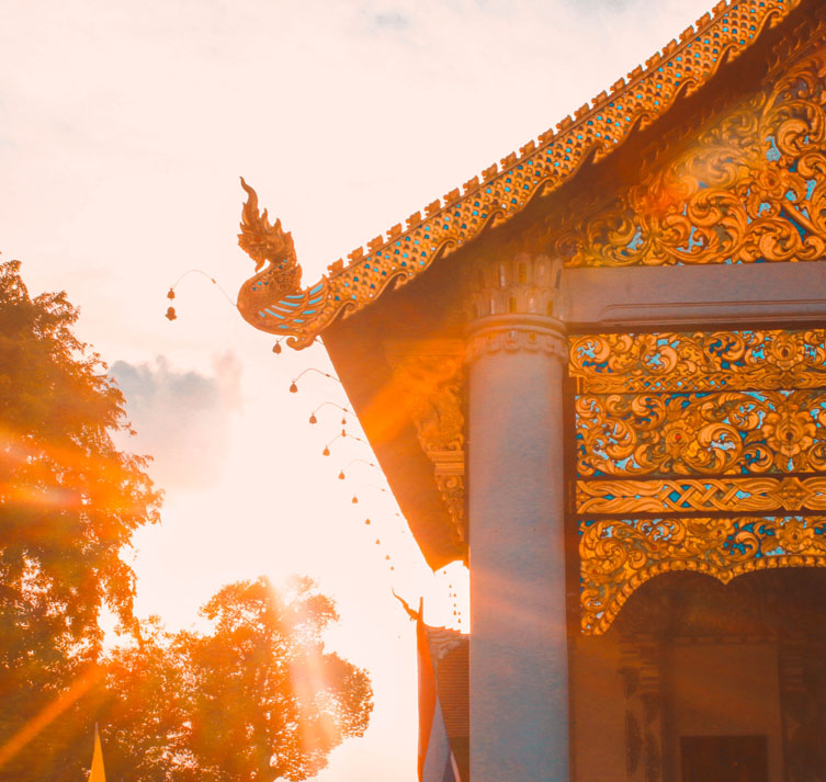Golden sunshine filters through trees casting light on a Thailand temple.