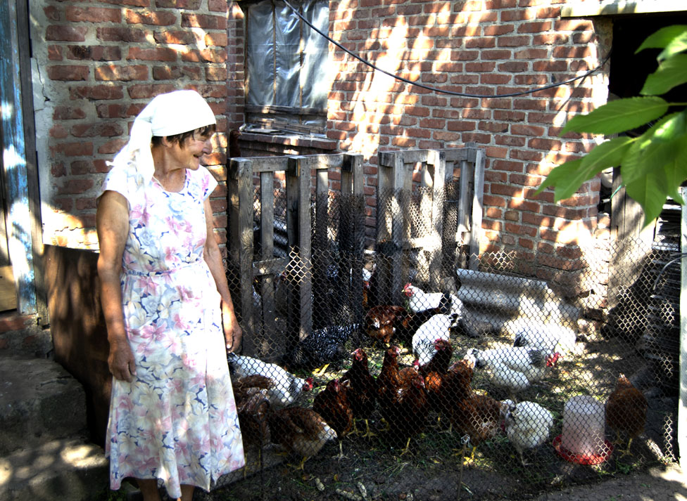 An elderly woman standing next to chickens in front of a brick wall