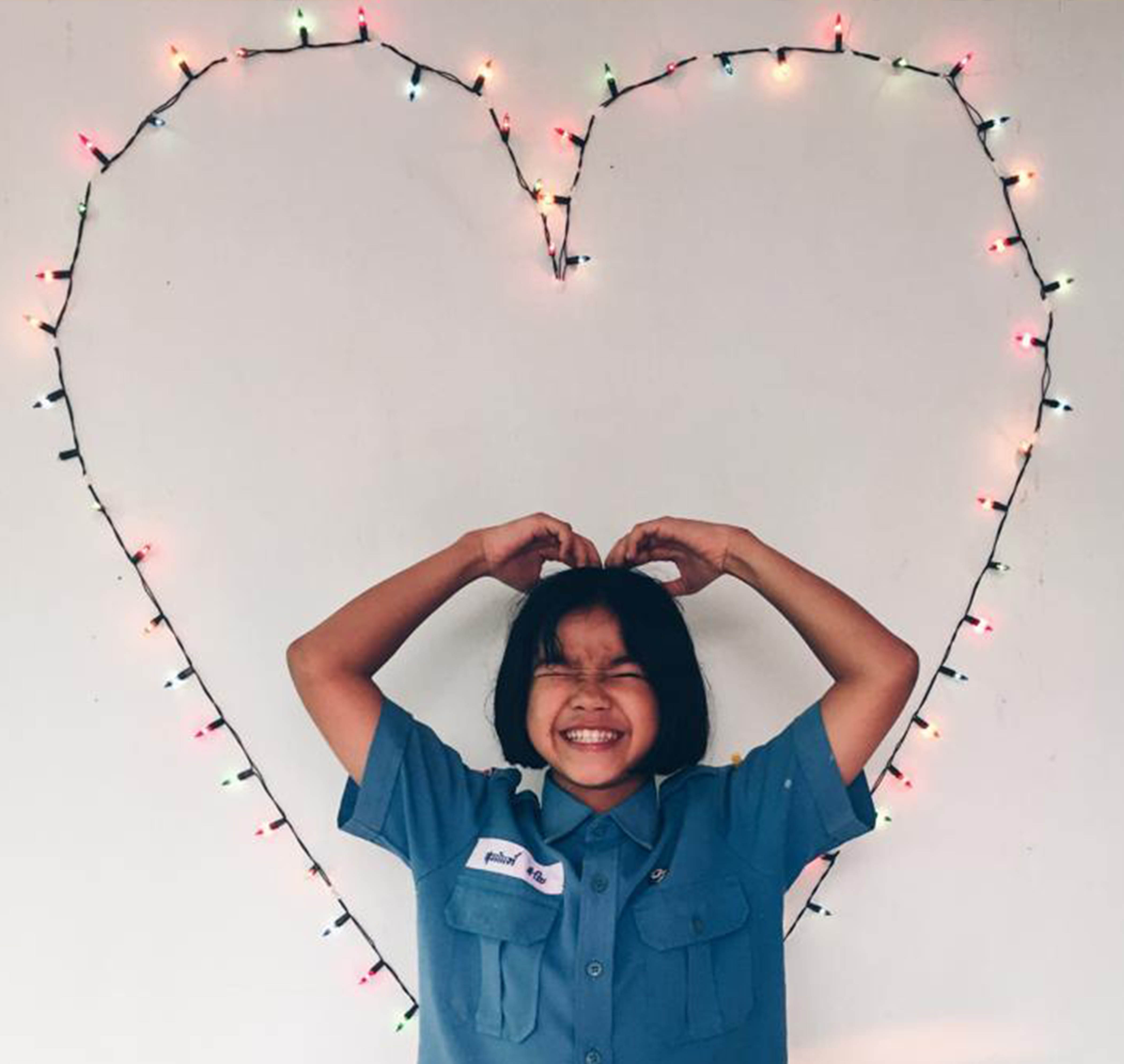 A young Thai girl in a blue shirt smiles and poses with a heart made out of fairy lights.