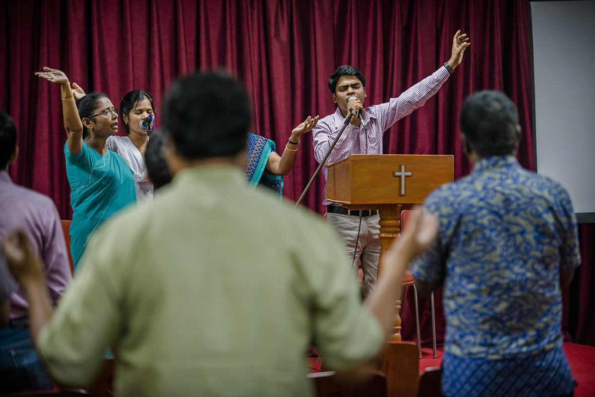 A man raises his hand in worship in front of a lectern.