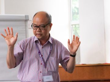 A man speaking with his hands up.