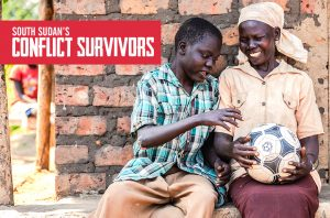 A mother and her son sitting on a doorstep smiling and holding a football in Uganda.